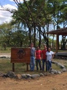 Lief And The Crew At Los Islotes Standing Next To A Wooden Sign That Says Panama Jacks With Tropical Trees In The Background