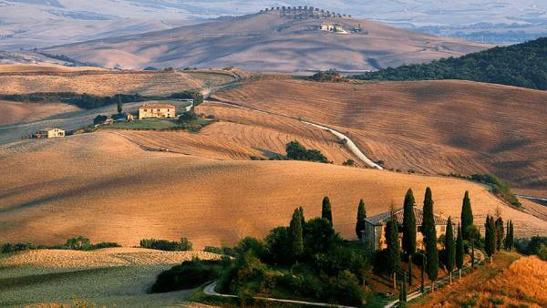 Rolling Tuscany Countryside with farm house, trees and winding roads.