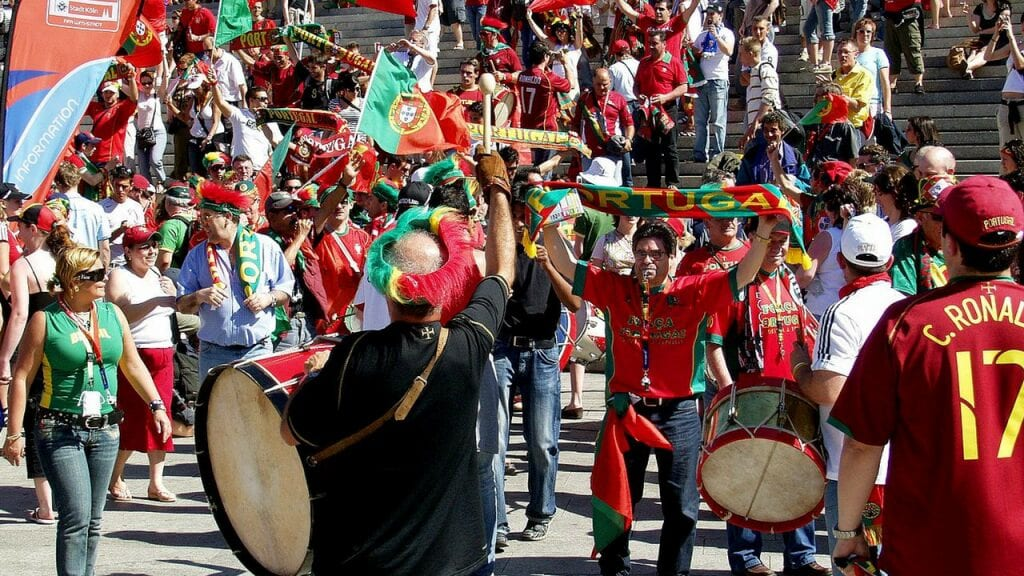 portugese football fans with drums, flags and football shirts milling about before a match