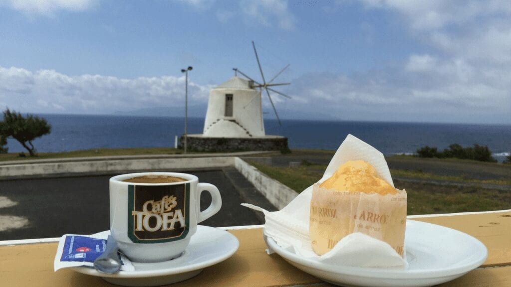 a cup of coffee and pastry on a table in front of a windmill by the sea