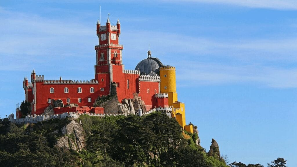 a red palace on top of rocky green mountain, portugal