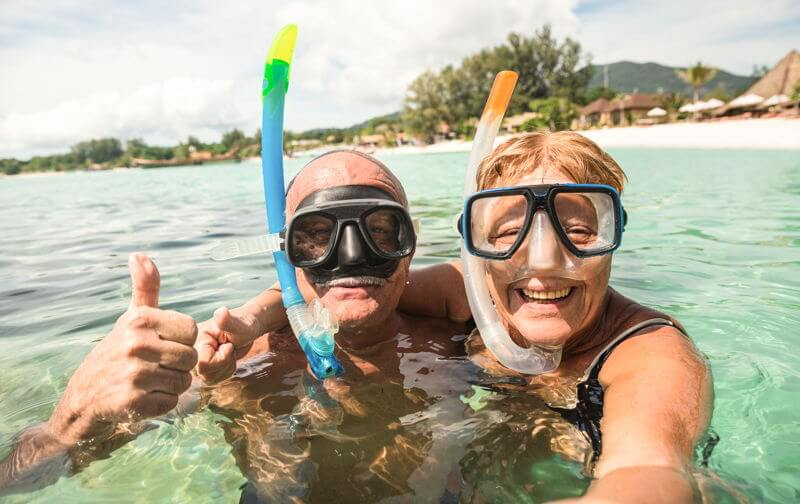 retired couple in sea with snorkelling masks