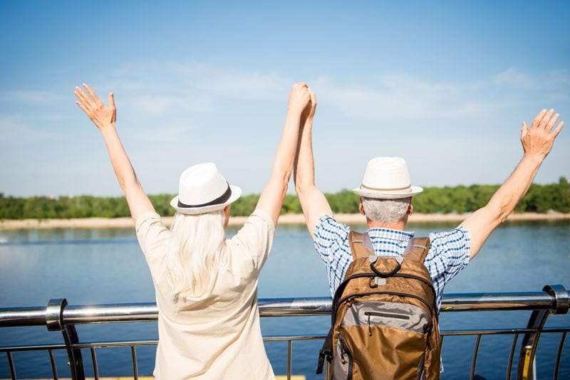 A happy retired couple travelling on a boat towards an island