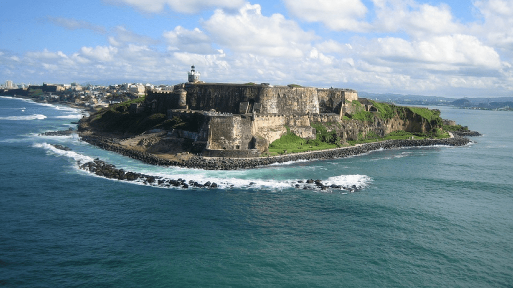 View from the sea of a castle in puerto rico. the castle is massive and you can see along the coaset and also surf breaking over the rocks