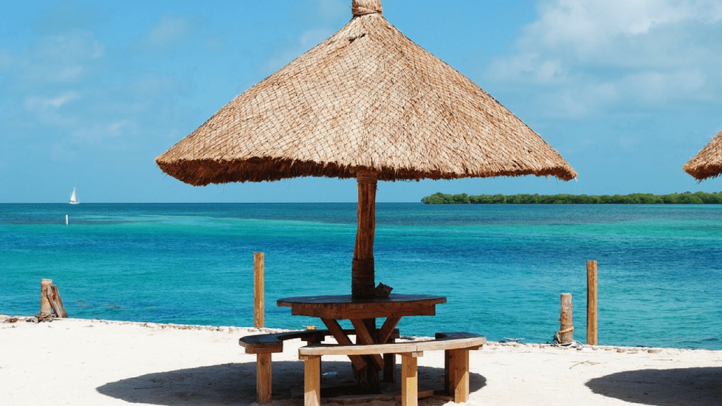 Ambergris Caye, Belize, white sand beach with wooden table and leaf umbrella. One of the Cheapest Places to Live in the Caribbean According to Forbes 2019