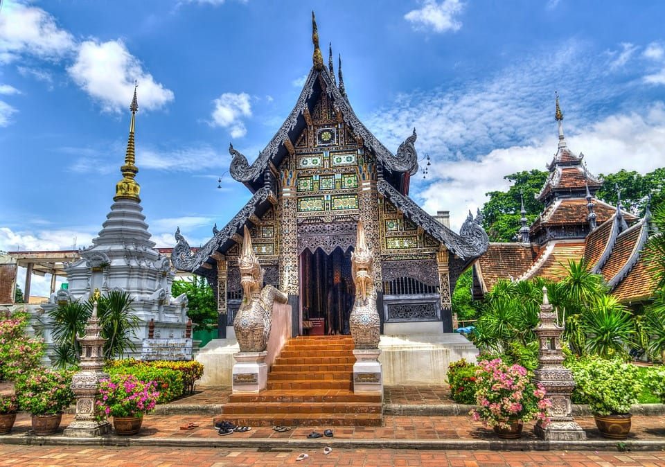 View from the front of a lush, verdant Buddhist temple in Chiang Mai, Thailand