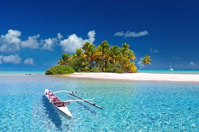 A white-sand beach on an island with a kayak and clear blue water.