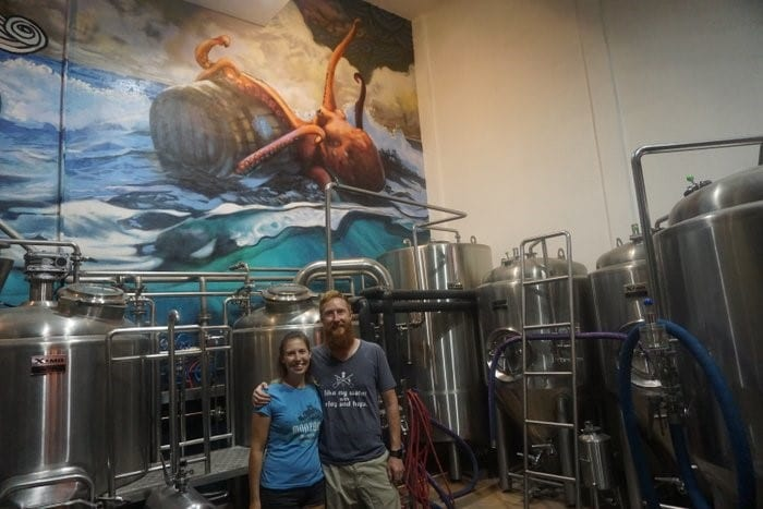 Owners of Monzon Brewing in front of a brewing vat