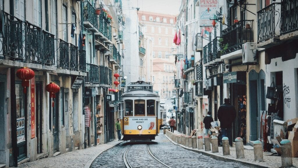 A vintage yellow tram climbs uphill along a street in lisbon, portugal