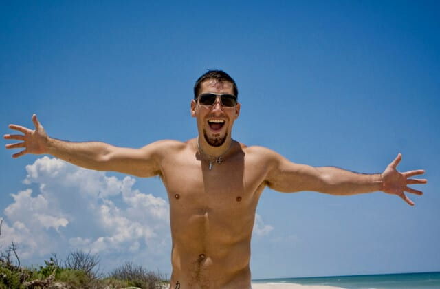 One of the world's best nude beaches. A male showing off his body at the beach with his arms out