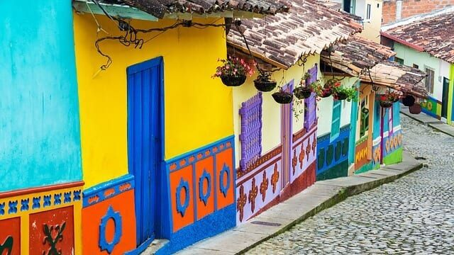 Brightly colored homes with flower baskets lining a cobblestone street in Colombia.
