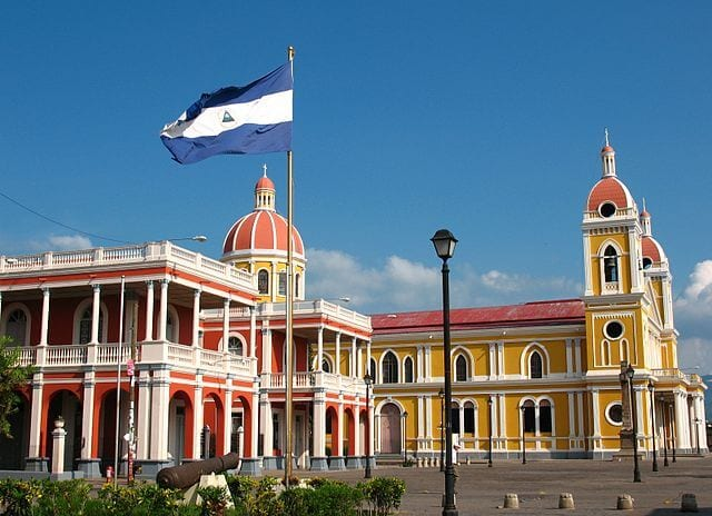 Old colonial buildings of orange and yellow with the Nicaragua flag waving in the air and a cannon out front.