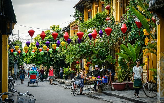 Hoi An Vietnam with yellow buildings and green foliage along a street and colorful lanterns hung over the street.