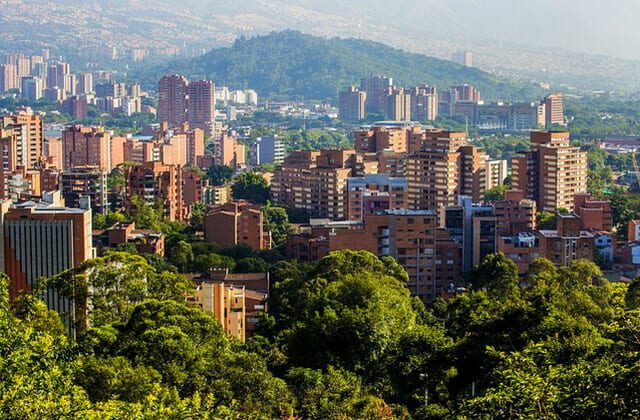 View of Medellin with lush green trees scattered between brick buildings.