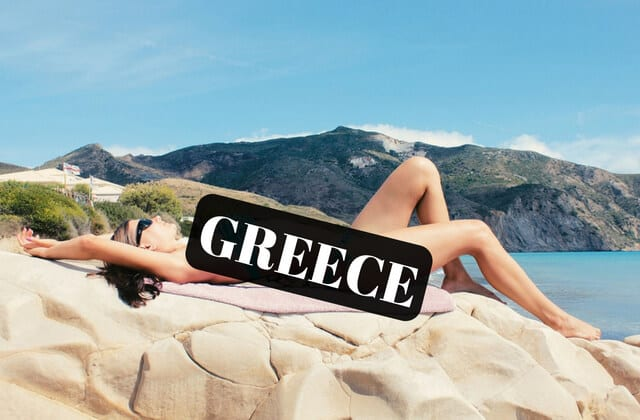 A nude woman laying on the rocks near the ocean in Greece covered by a black box saying Greece.