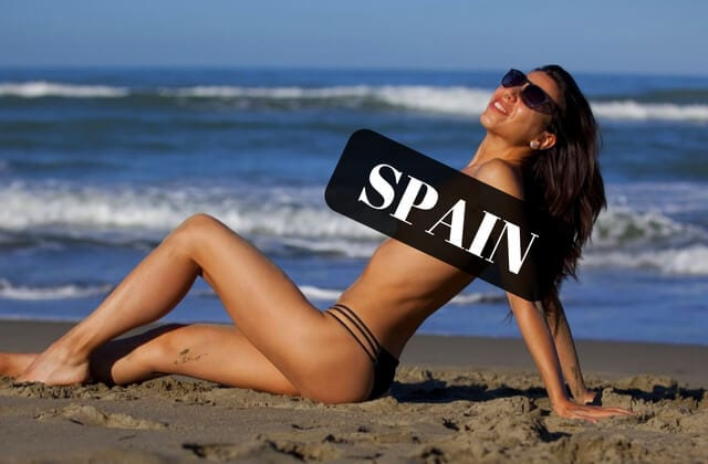 A female nudist laying on the beach in Spain covered by black box saying Spain.