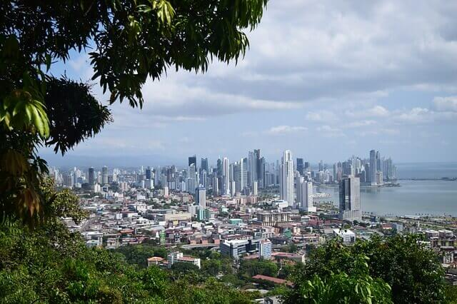 Panama City, Panama shines beyond the thick foliage of trees giving an overview of the majestic city.