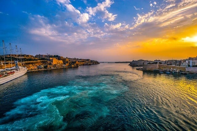 Sun shines over the historic harbor of Valletta, Malta.