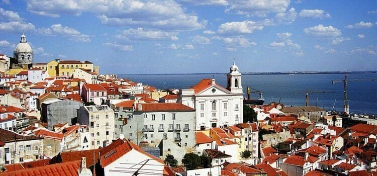 A view of the orange roofed, white buildings throughout Lisbon, Portugal