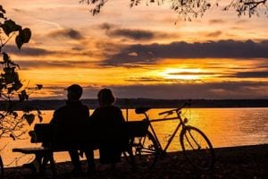 Couple sitting together on a bench watching the sunset, while enjoying the benefits of the Belize QRP Program.