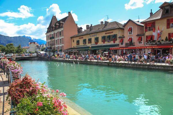 view across the canal of people enjoying food and drink outside in annecy, france