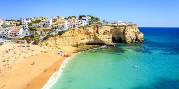 View of the Carvoeiro beach on the Algarve, Portugal. Yellow sand and clear, blue sea