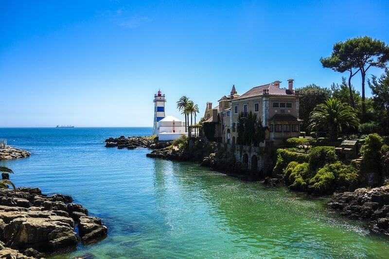 lighthouse in cascais portugal under clear blue skies with clear green waters