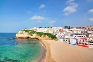 A view of the coast of the Algarve region in Portugal, with blue and green water and bright trimmed houses.