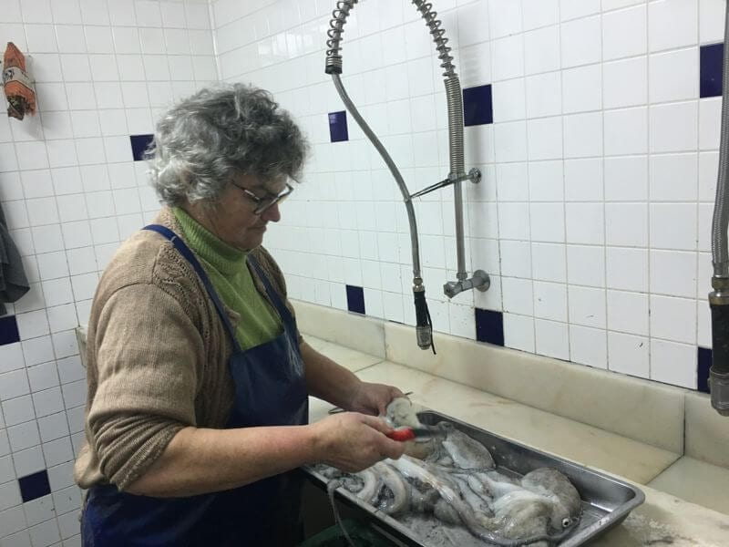 lady preparing octopus in algarve portugal