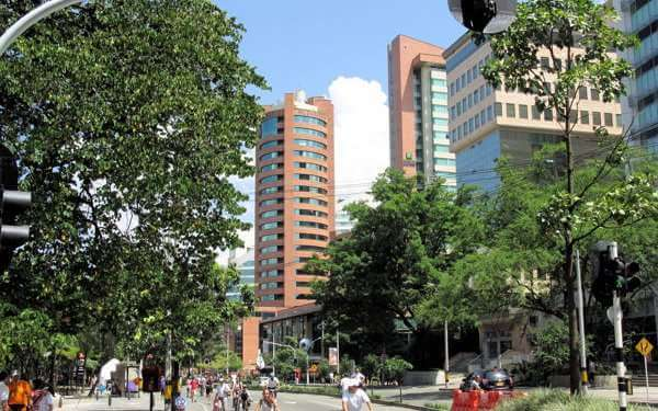 el poblado medellin colombia. A view fromt he street, trees, people and buildings in the background