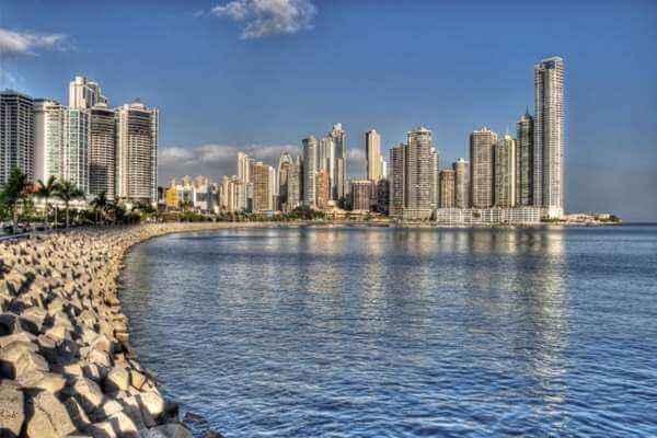 view across panama bay of panama city. Breakwater stones, ocean and buildings on the shore.