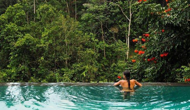 Woman in an outside pool in the Bali jungle. Best places to honeymoon