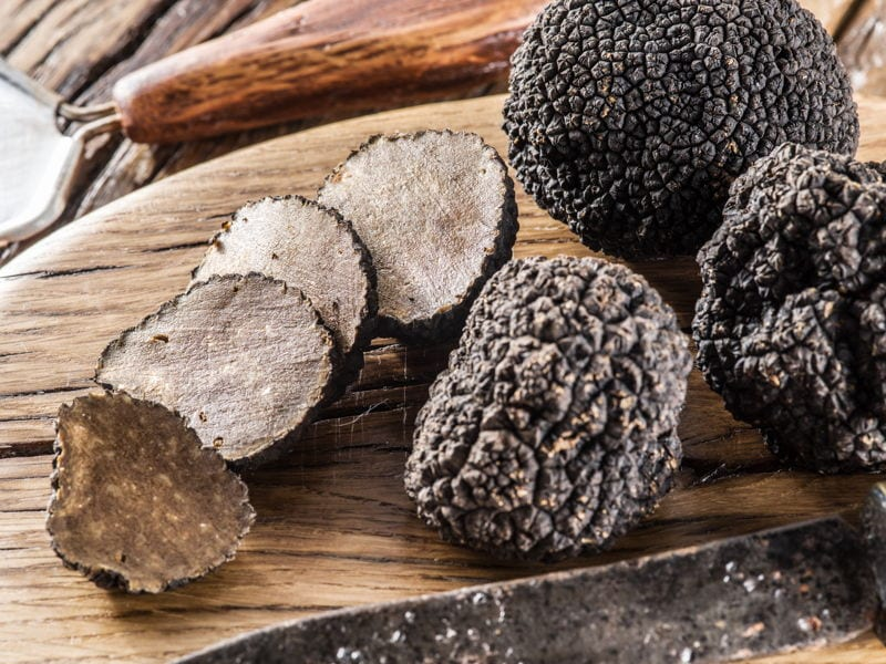 Black truffles on a wooden chopping board