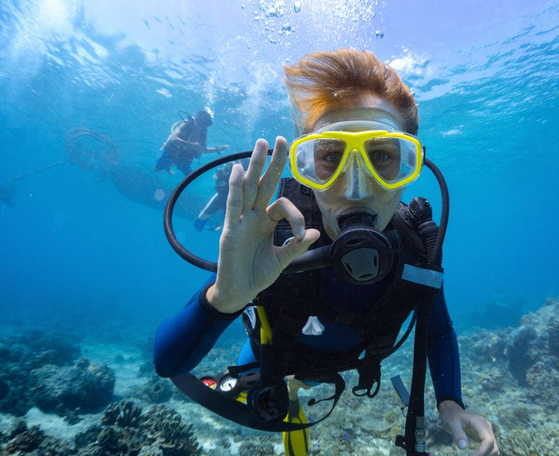 Woman scuba diving in tropical waters making OK hand sign. The Best Places In The World To Scuba Dive