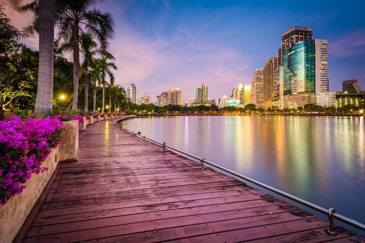 Modern skyscrapers, flowers, and palm trees along Lake Rajada at sunset, at Benjakiti Park, in Bangkok, Thailand.