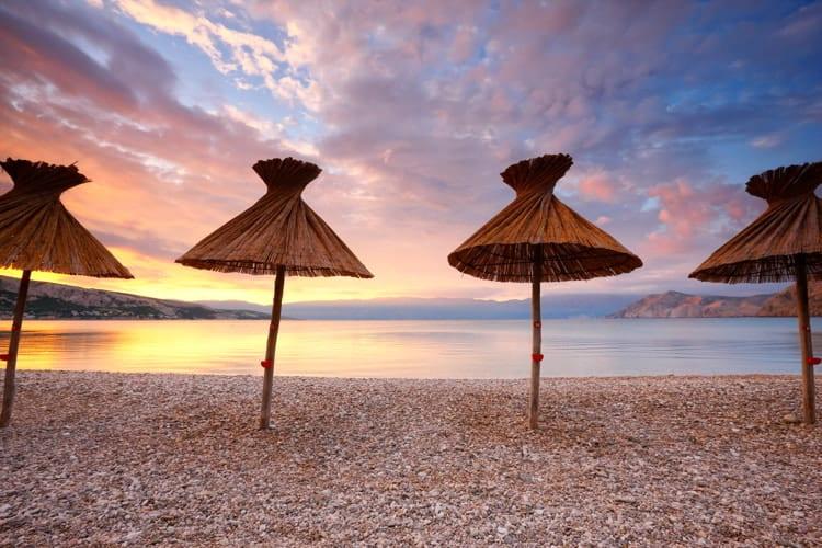 Straw umbrellas on the beach in Baska, Croatia