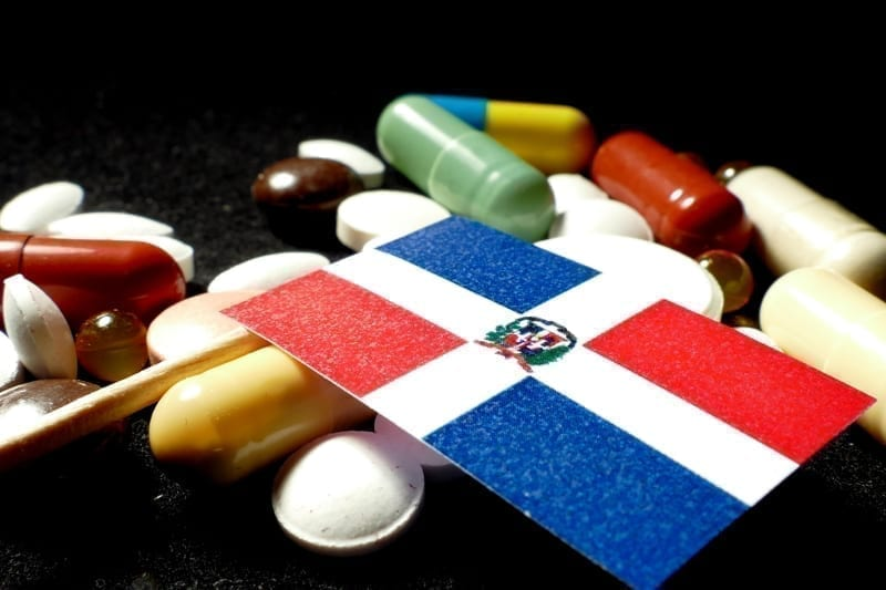 Dominican Republic flag with lot of medical pills on black background