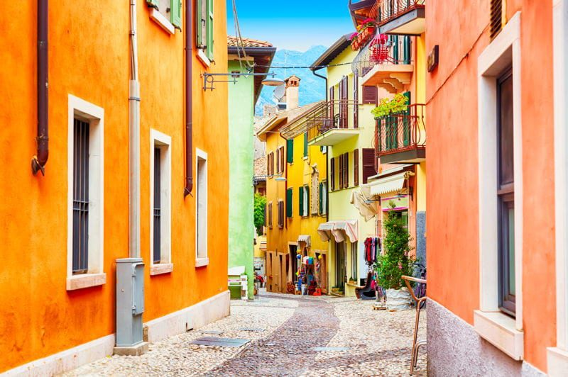 Quiet street with colorful houses in Italy. Find out how real estate overseas can protect your assets