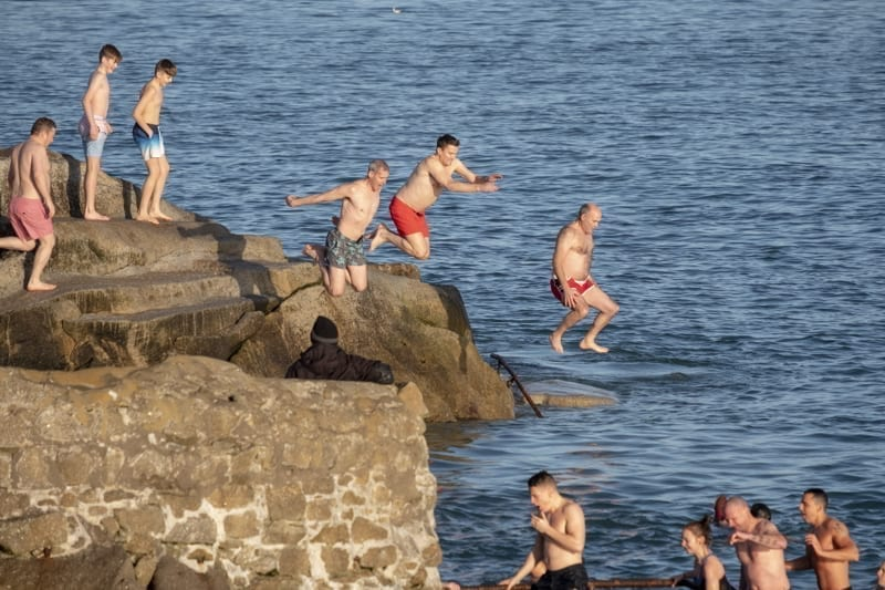 People jumping into the sea at Forty Foot during Christmas traditional swim.