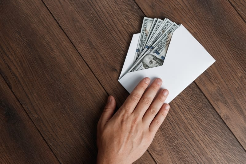 Man's hand and U.S money in a white envelope.
