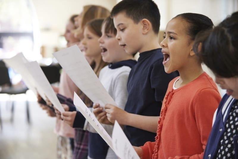Group Of School Children Singing.