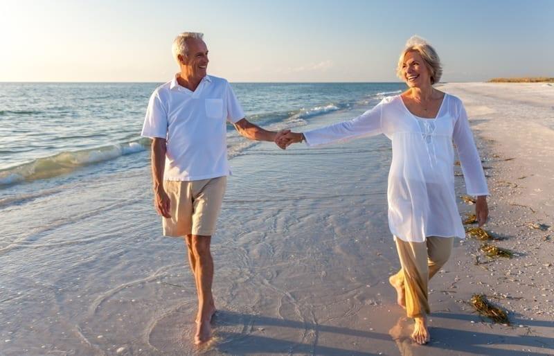 Retired couple walking in a beach.
