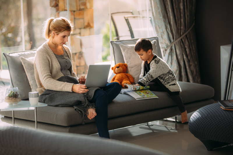 mother working from home while son plays on tablet