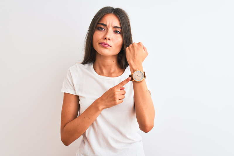 an impatient woman pointing to her watch