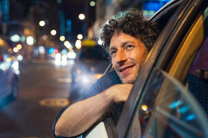 man in back of taxi smiling looking at sights