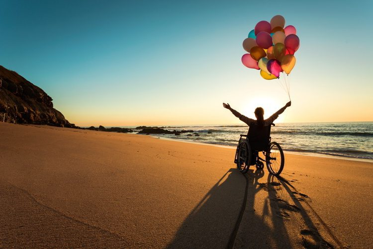 A person on a wheelchair with colorful balloons at the beach