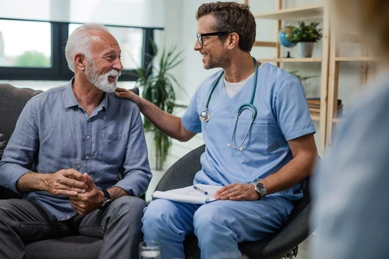 Happy doctor talking to senior male patient while being in a home visit