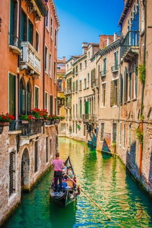 Beautiful scene with traditional gondola on a canal in Venice, Italy