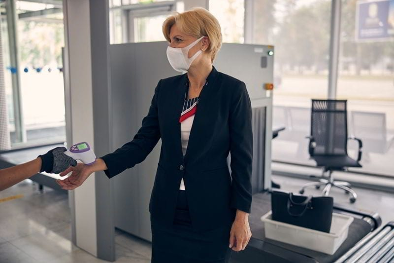 Airport worker using digital medical thermometer while checking body temperature of businesswoman.