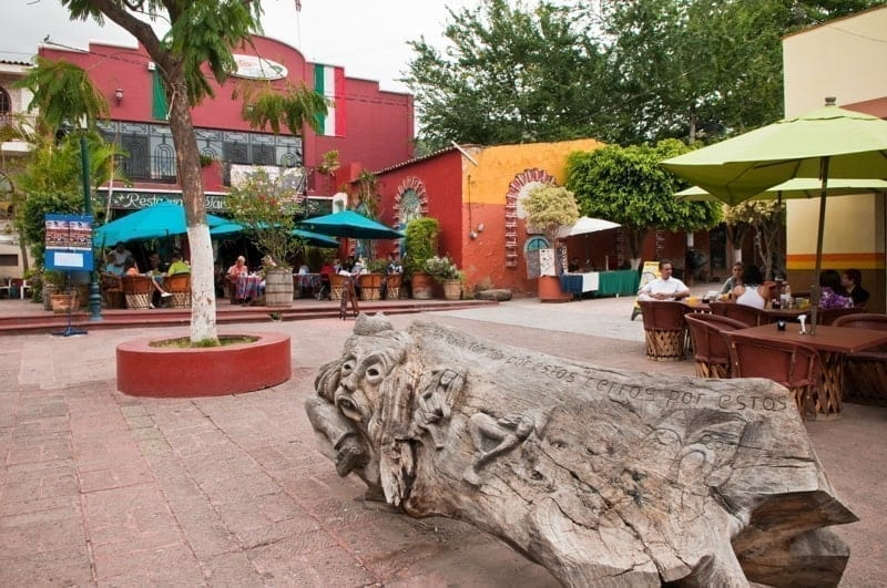 Wooden sculpture and cafes on the main plaza in Ajijic, Mexico